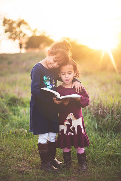 Photo of two happy girls reading a book together.
