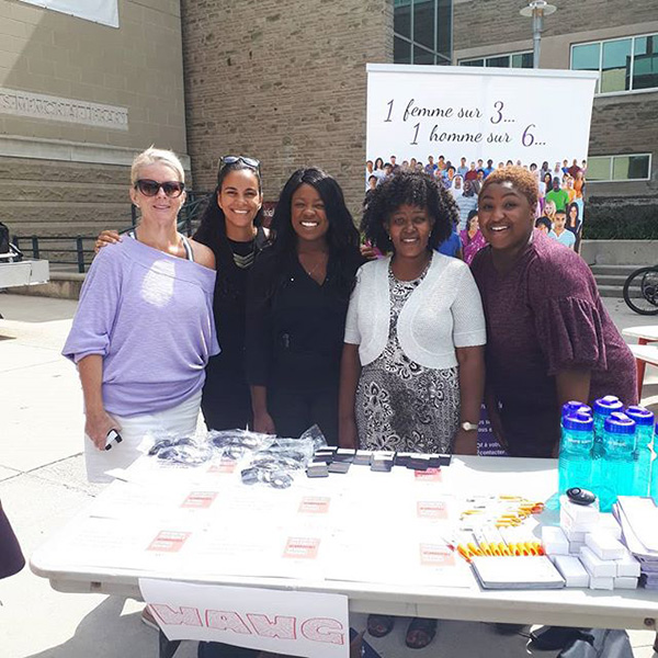 Events page photo of five women who are part of the Women Abuse Working Group organization. They are standing outside of the McMaster University buildings with a display booth. WAWG@McMaster Welcome Week Resource Fair