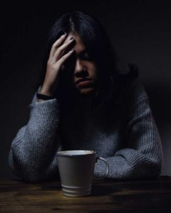"Photo of a woman with a bad headache. This image is a link to the ""What is Abuse?"" page."